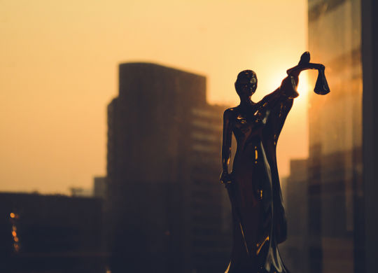 Law concept. Silhouette of Themis with building background. Statuette of justice. Statuette of the goddess of justice