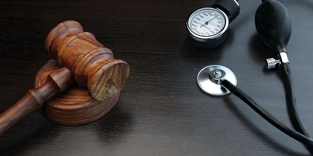 Judges Gavel And Medical  Stethoscope On The Black Wood Background, Close-up, Top View