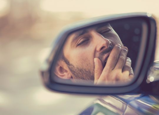 side-mirror-view-sleepy-tired-yawning-man-driving-car-picture-id586390674